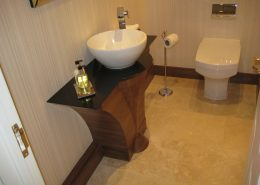 Shaped american black walnut pedastel with vanity basin mounted on granite work top